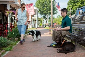 A blind man relaxs in town with his chocolate Lab guide dog